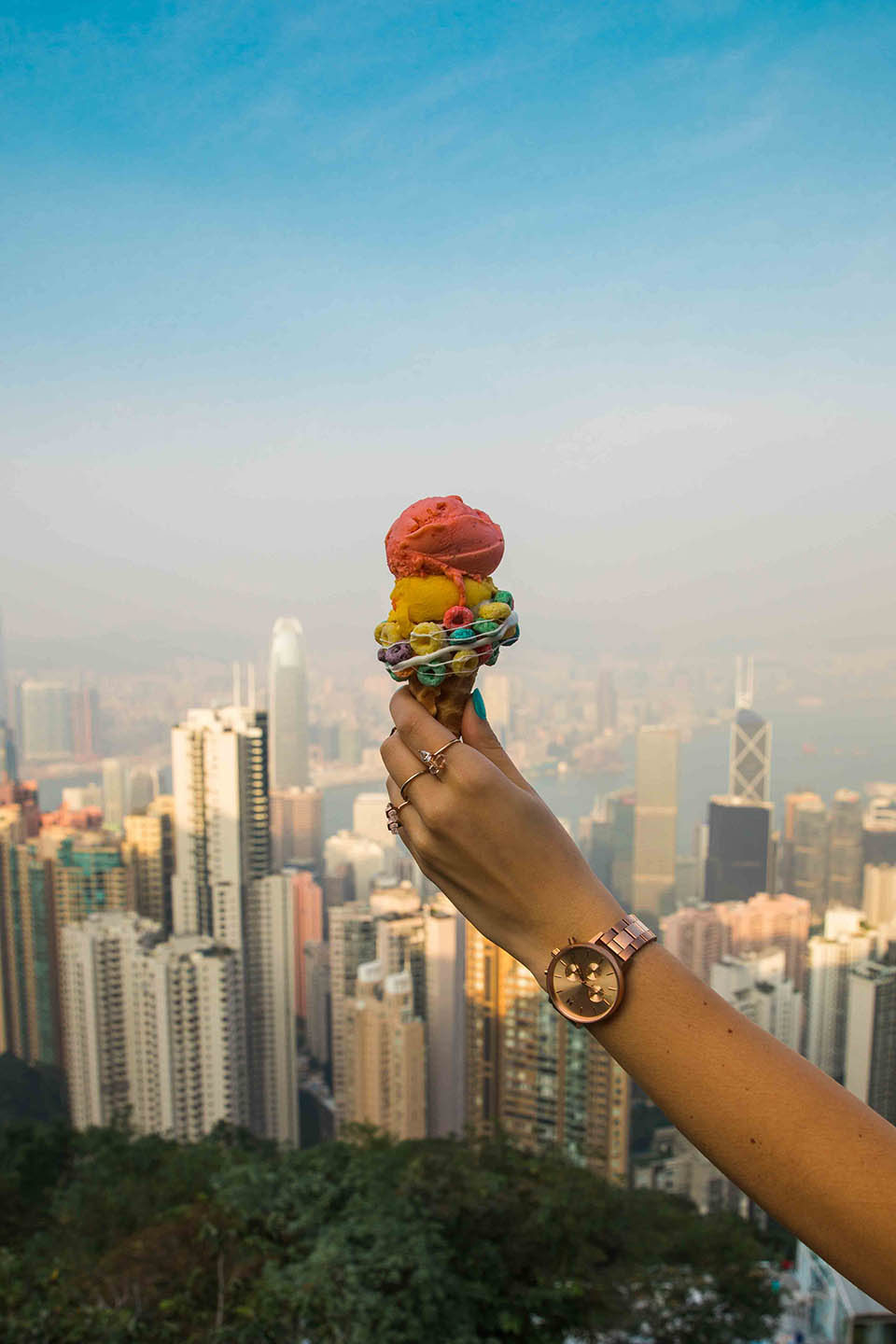 hand holding ice cream cone with Hong Kong in the background