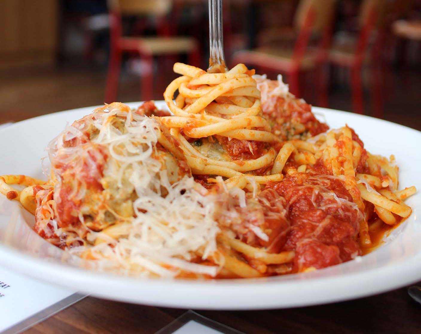 plate of spaghetti and meatballs with fork sticking up