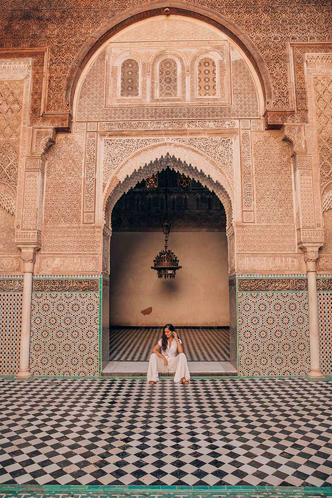 woman seated in ornate doorway of Moroccan temple