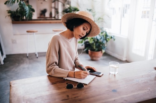 woman in hat writing on desk