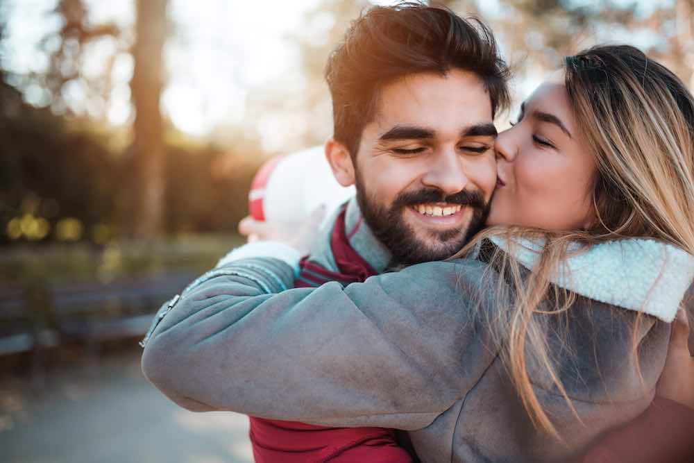 man with beard being kissed on cheek