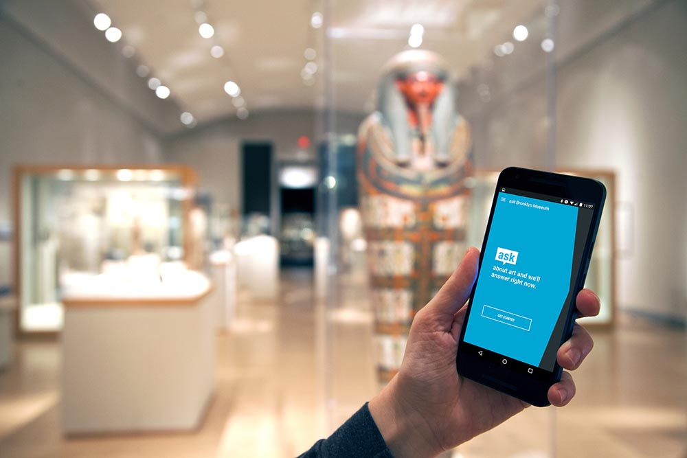 hand holding mobile device displaying museum tour web app