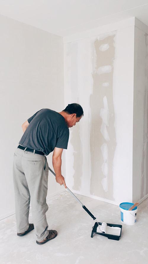man painting wall with fresh coat of white paint