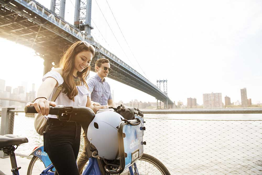 couple walking with bicycles under bridge