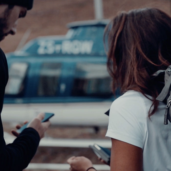 woman and man checking phones before boarding a helicopter