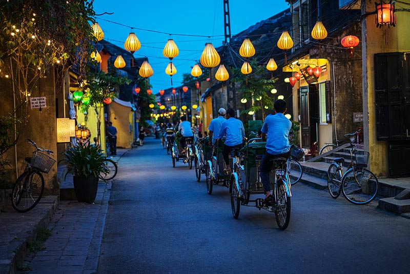 a group of bicycle cabs pedal down a dark street with lanterns along sides of the buildings