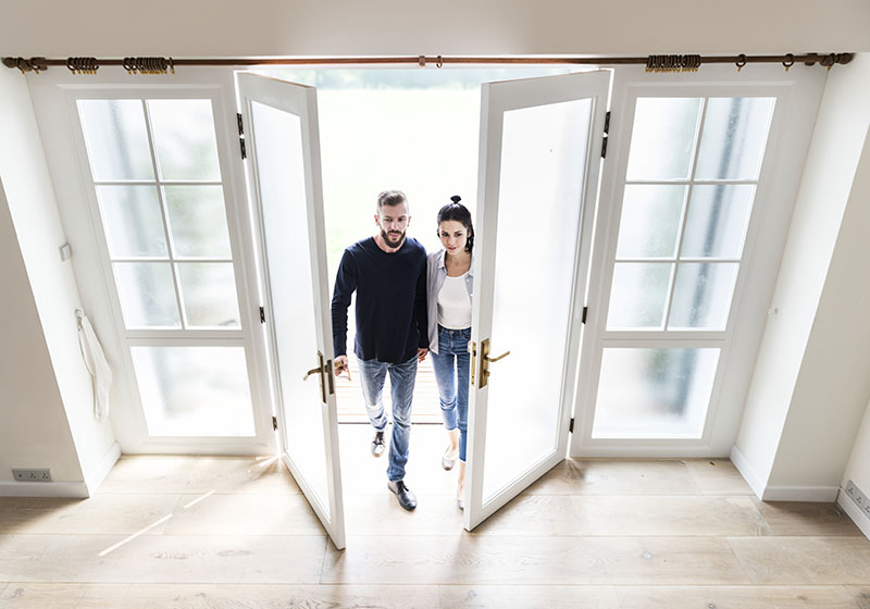 Overhead shot of trendy couple walking through a set of french doors