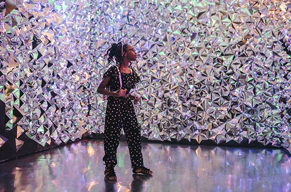 young girl in black jumpsuit walking through a room covered in iridescent shapes