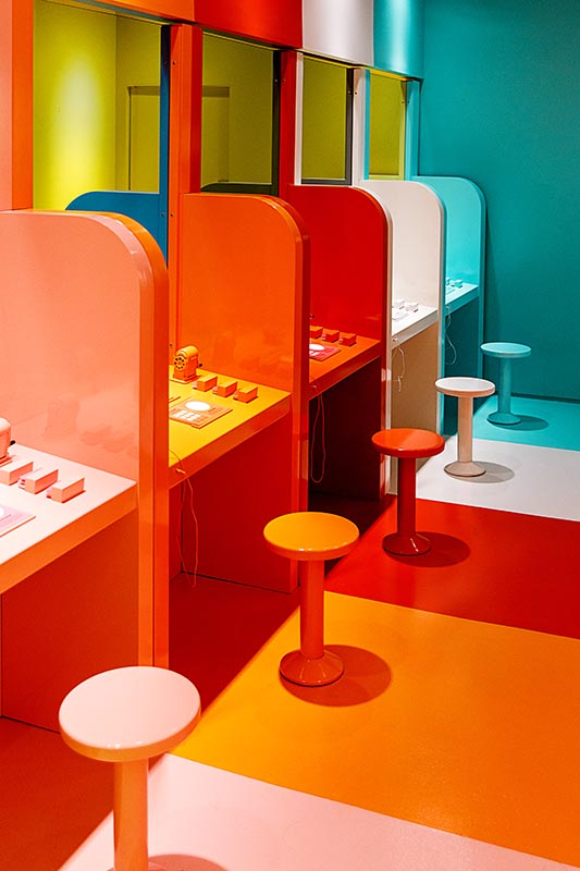 A line of multicolored stools and booths in bright colors