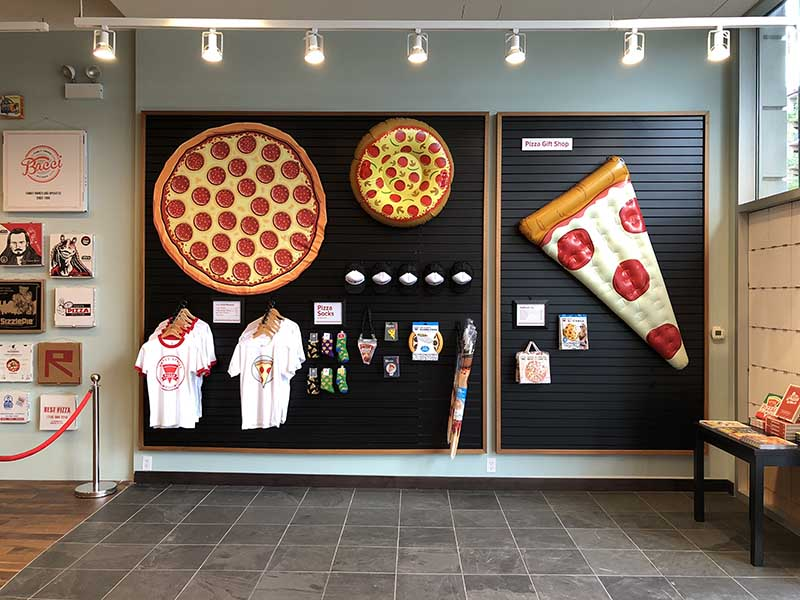 wall of the gift shop of the pizza museum showcasing t-shirts and knick-knacks for sale