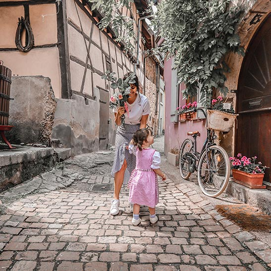 Carolina Fryer plays with her daughter on a cobblestone street while holding a plant