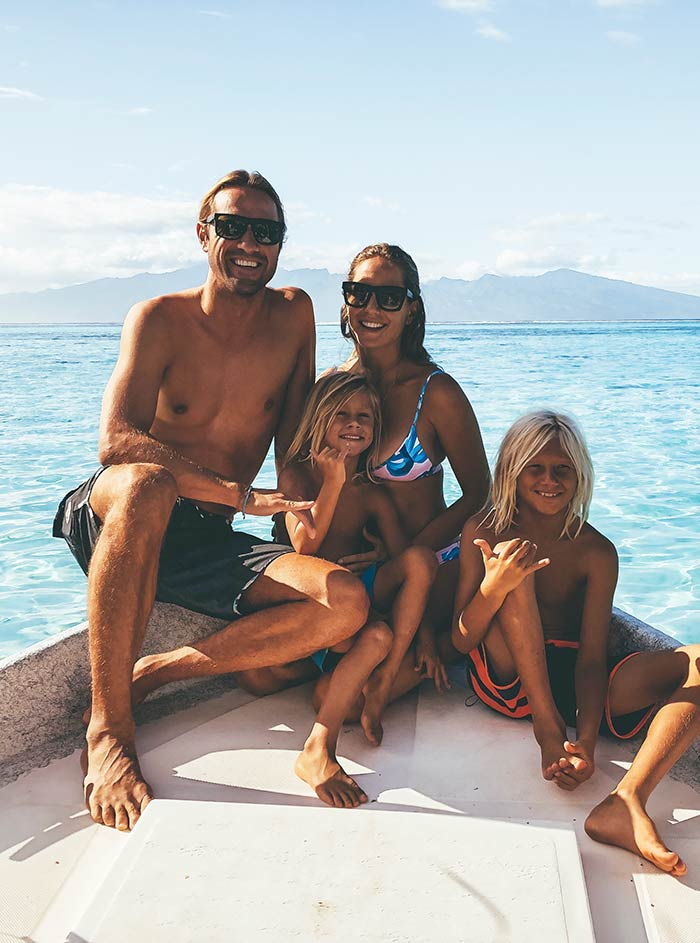Andrea Hannemann with her husband and two children sitting on a boat on the water in Hawaii