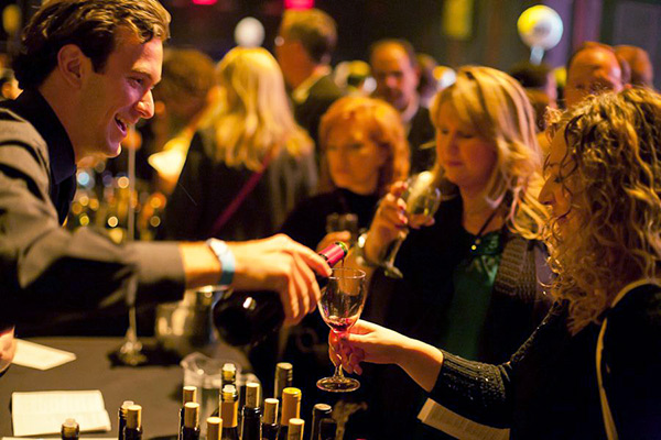 A man pours wine for 2 women at a wine tasting