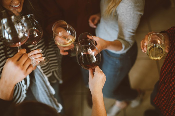 a group of friends doing a cheers with glasses of wine