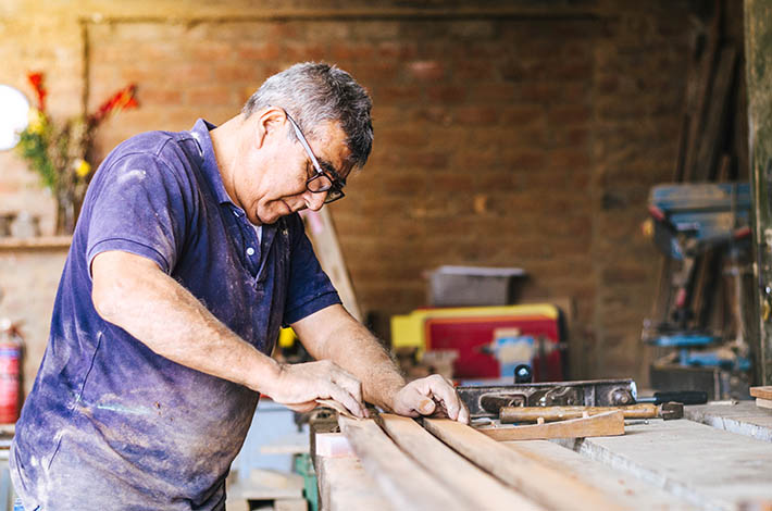 an older man wearing protective eyewear stands at a work shop sanding and cutting wood
