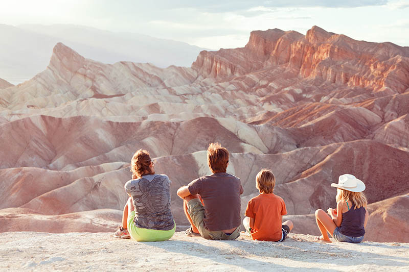 A family with 2 kids sit on the ground looking out at mountain scenery