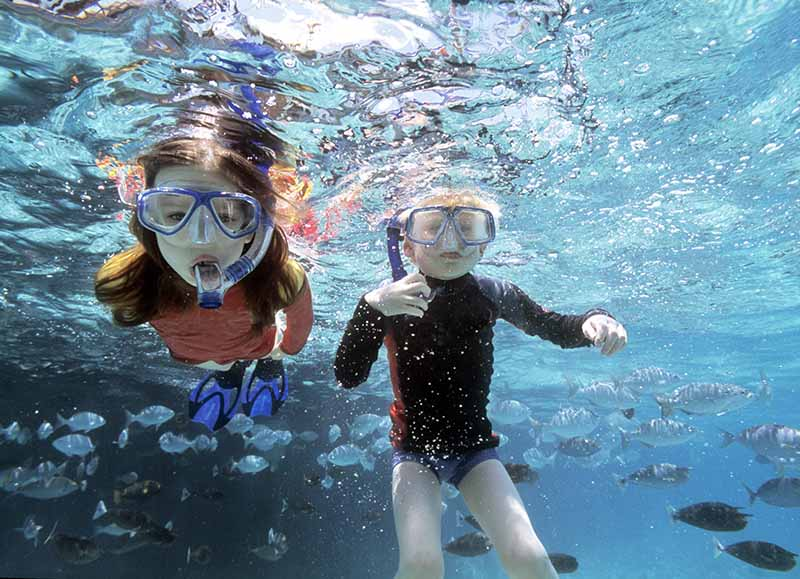two young children underwater look at the camera through their goggles