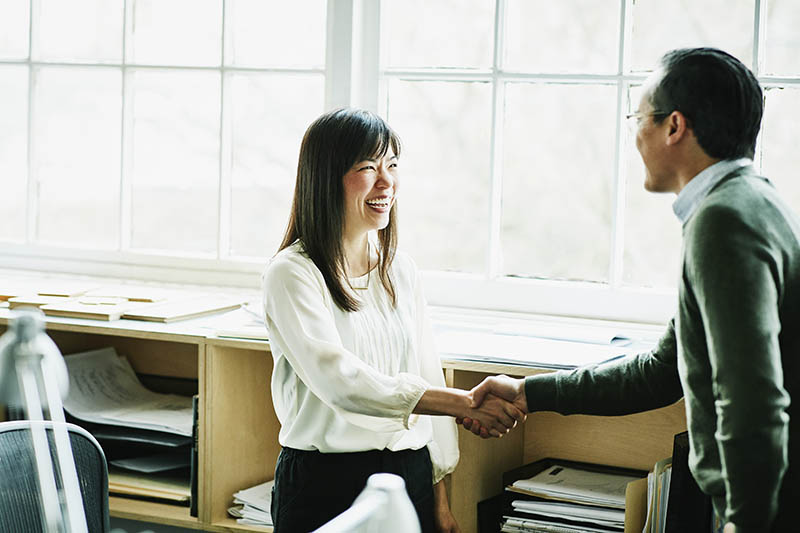 Asian businesswoman shaking hands with a coworker