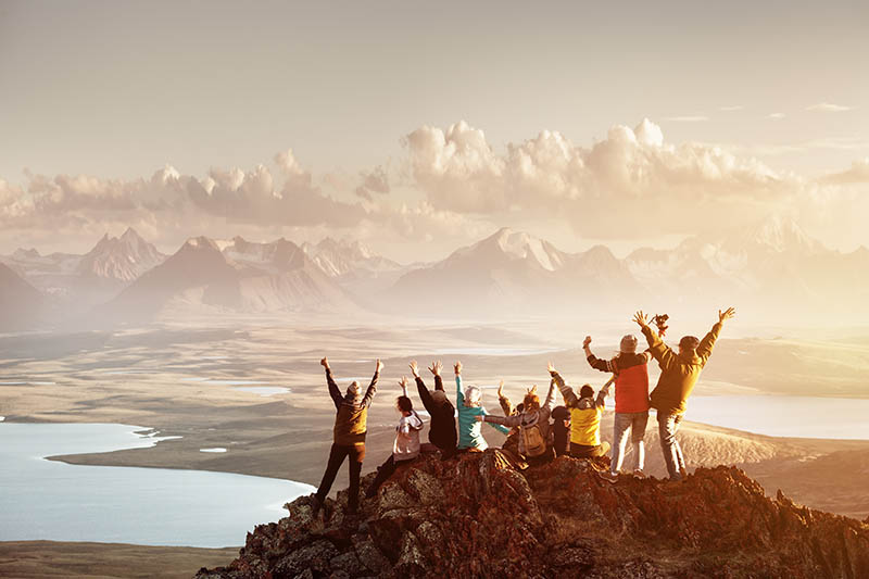 a group of friends celebrate with their hands in the air at the top of a mountain