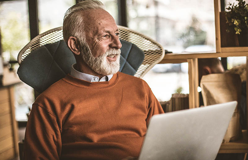 Man with white hair and a white beard in an orange sweater sits in a chair with a laptop in his lap