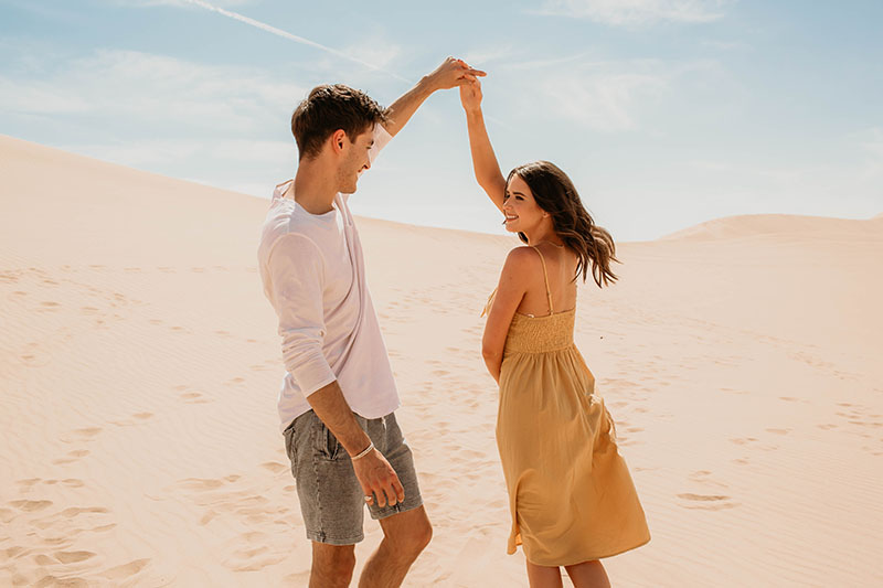 Influencers Jess and Gabriel Conte hold hands and dance together in front of desert landscape