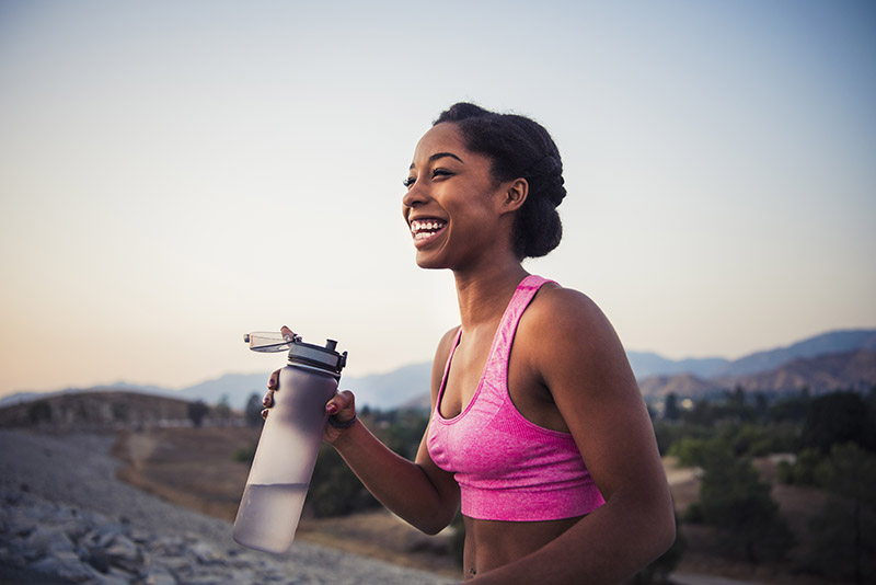 Athletic African American woman smiling as she holds a modern water bottle during a run