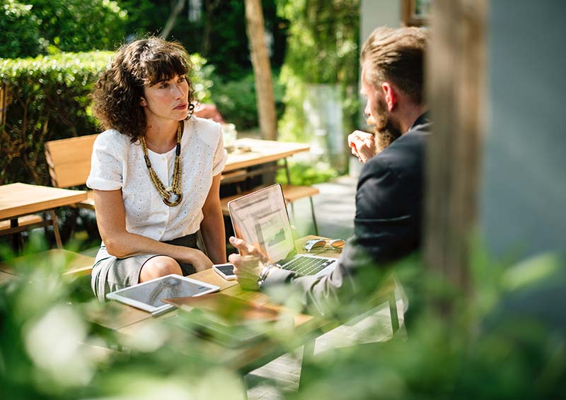 a view of a woman and a man at a table with a laptop in an outdoor cafe as they discuss something serious