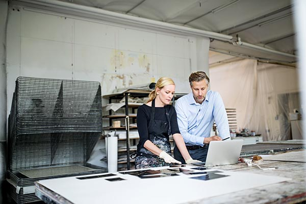 a woman and a man stand together over a work table while looking at a laptop