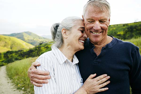 Happy older couple embracing as they walk though a green field