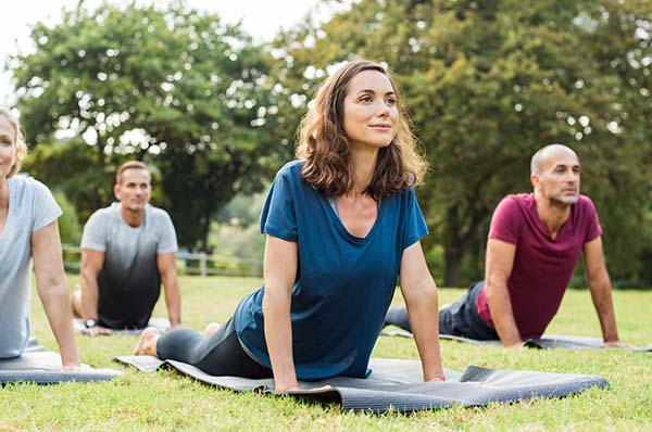 Woman and 3 men doing yoga in a field