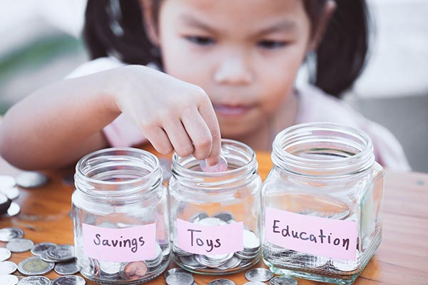 "young girl dividing coins into 3 different jars. From left to right, one jar is labeled ""savings"", and the last jar is labeled ""toys"", the last jar is labeled ""education"""