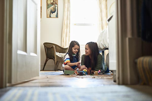 mother and daughter playing with toys on the floor