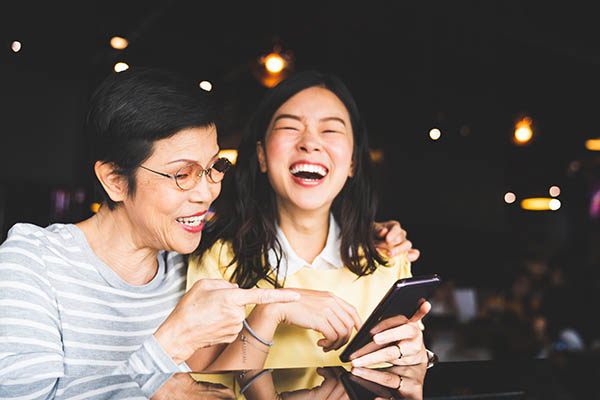 Asian mother and daughter laughing while looking at a mobile phone