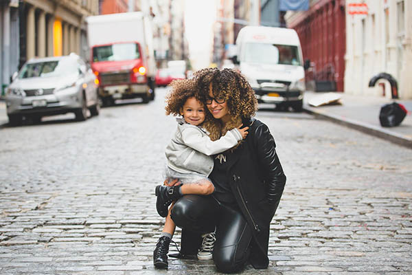 mother and young daughter hugging in the middle of a city street