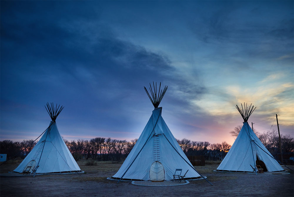Three Tee pees in a field at dusk