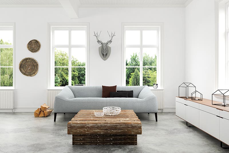 white walled living room with a gray couch, a low wooden table and a gray wooden cardboard deer head mount on the wall