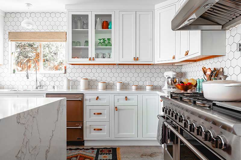 white and light wood kitchen with a honeycomb pattern white tile backsplash