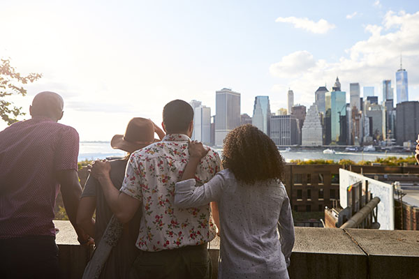 group of friends watching the sunset over a city skyline