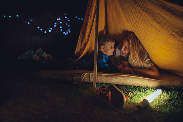 mother and son in a backyard tent at night smiling at each other