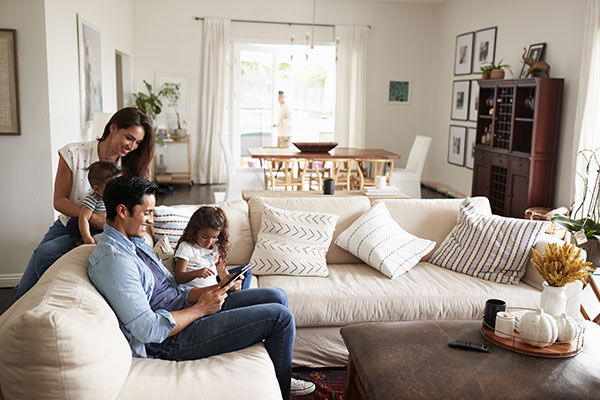 young family sitting on sofa reading a book together in their living room