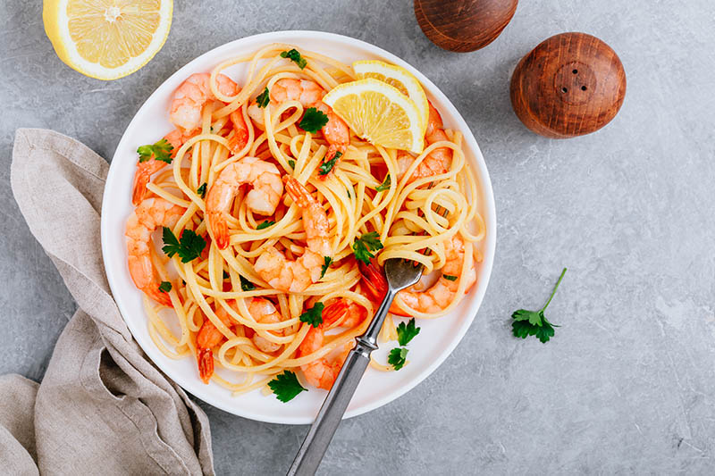 Seafood Pasta spaghetti with shrimp and parsley on gray stone background