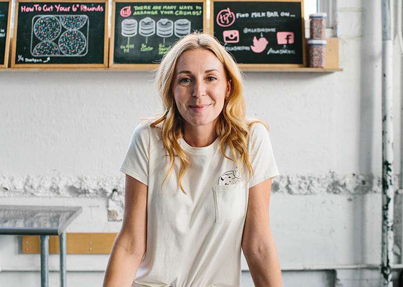 Closeup of Christina Tosi in her kitchen in front of chalk lettered baking signs.