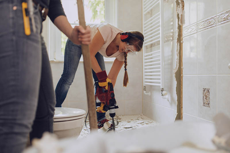 Woman works on remodeling her bathroom