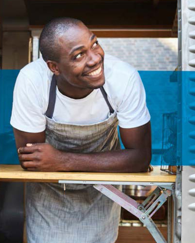 man in apron leaning out food truck window smiling